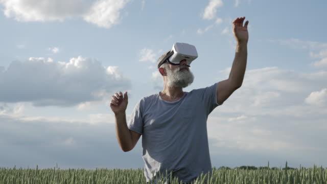 älterer mann bewegte objekte in der virtuellen realität - schutzbrille stock-videos und b-roll-filmmaterial