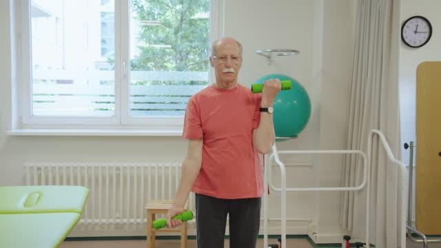 elderly man picking up dumbbells at health club - rehabilitation center stock videos & royalty-free footage