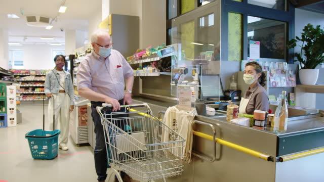älterer mann kauft lebensmittel im supermarkt - computeranlage stock-videos und b-roll-filmmaterial
