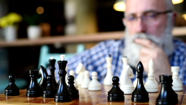 elderly man puts mate in chess - plaid shirt stock videos & royalty-free footage