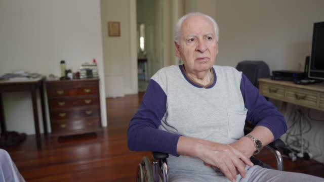 vidéos et rushes de homme âgé s'asseyant dans un fauteuil roulant dans une maison de soins infirmiers - être seul