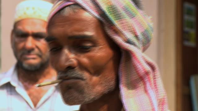 vidéos et rushes de cu elderly man smoking cigarette / rajkot, india - cigarette