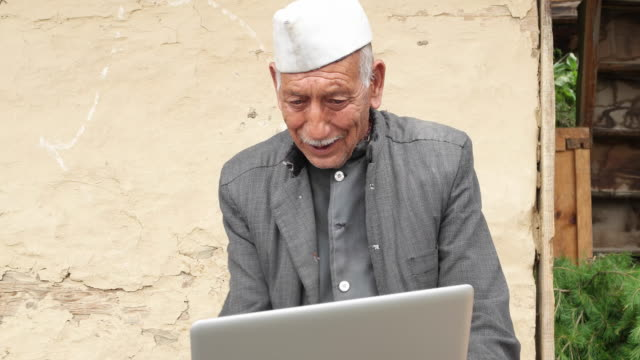 Elderly man using a laptop seated