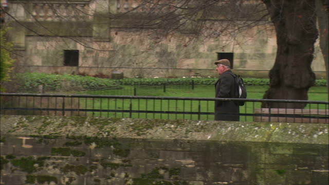 ws pan elderly man walking along riverbank / bath, somerset, united kingdom - one man only stock-videos und b-roll-filmmaterial