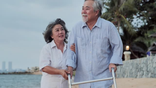 elderly man walking with walker on the beach and elderly woman in summer.senior couple relaxing by the sea on sunny day ,senior holidays,healthcare and medicine,vacations - walking frame stock videos & royalty-free footage