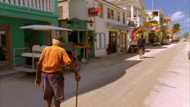 Elderly man walks along quiet street using stick as young boy rides past on bike, Belize Available in HD.
