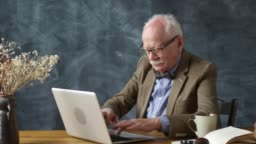 Elderly Man with Bowtie Typing on Laptop