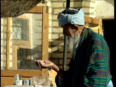 elderly man with cane handles beans from sack at market stall bukhara uzbekistan - bukhara stock videos and b-roll footage