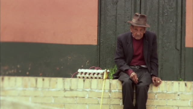 ms elderly man with fedora and cane sitting on ledge as woman walks past / bogota, colombia - ledge stock videos & royalty-free footage