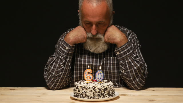 elderly man with sad look on the anniversary cake