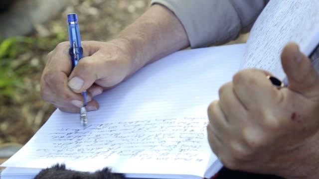 elderly man writing in his notebook - 年配の男性一人点の映像素材/bロール