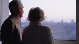 Elderly married couple standing by window together, caring husband hugging wife