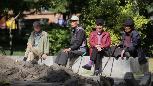 Elderly men chat as they sit on steps at Tapgol Park in the Jongrogu area of Seoul South Korea on Wednesday Oct 23 General views elderly men sit on...