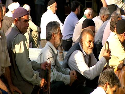 elderly men socializing outside of qom shrine / qom, iran - letterbox format stock videos & royalty-free footage