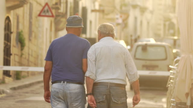 Elderly men walk in Marsaxlokk, Malta