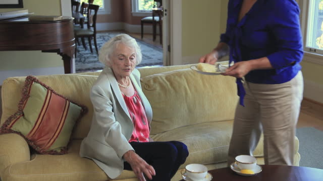 MS Elderly mother with adult daughter having tea in living room / Portland, Oregon, USA