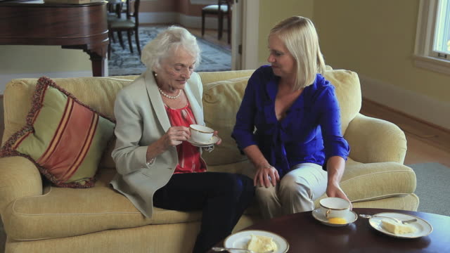 ms elderly mother with adult daughter having tea in living room / portland, oregon, usa - medium length hair stock videos & royalty-free footage