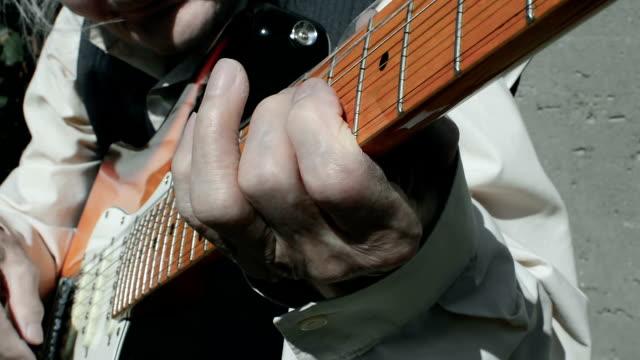 Elderly musician playing guitar.