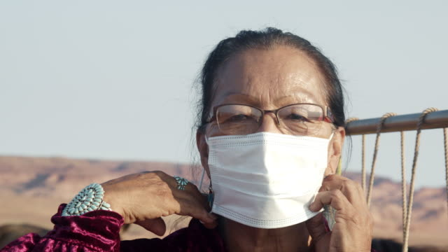 elderly native american navajo woman outside at the monument valley tribal park in front of a traditional weaving loom using an n-95 covid corona virus mask to flatten the curve and stop the spread during the pandemic - indigenous north american culture stock videos & royalty-free footage
