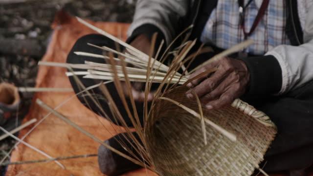 Elderly Nepalese man weaves basket, close up
