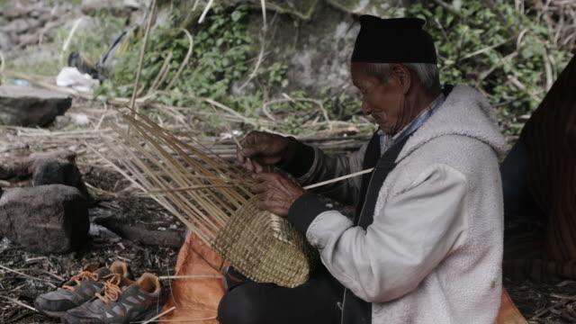 Elderly Nepalese man weaves basket