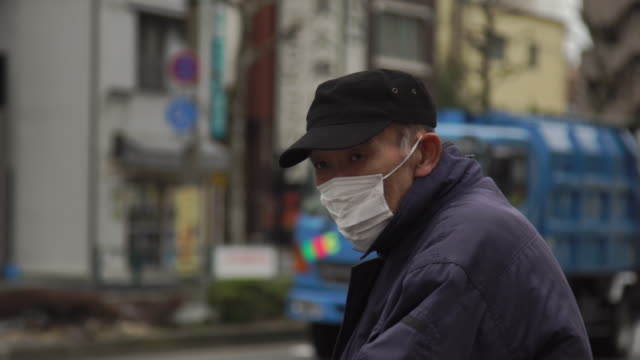 elderly pedestrian in face mask - japan - 保護マスク点の映像素材/bロール