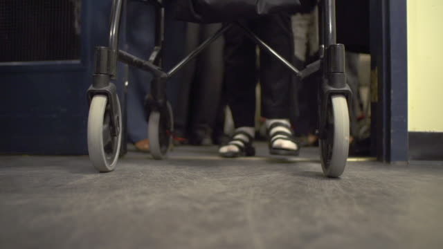 vídeos de stock e filmes b-roll de elderly people coming out of an elevator with walkers - disability