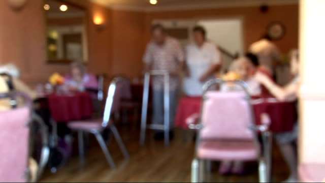 Elderly people living in a care home Blurred focus shots of male and female residents sitting down in canteen including man being helped along on...