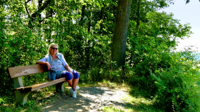 elderly people sit on a bench in spring - frau stock videos & royalty-free footage