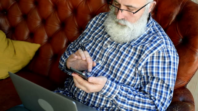 elderly professor is typing a message on a smartphone - plaid shirt stock videos & royalty-free footage