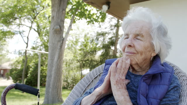 elderly senior caucasian christian woman with folded hands praying with her eyes closed in a lawn chair outdoors in the summer - widow stock videos & royalty-free footage