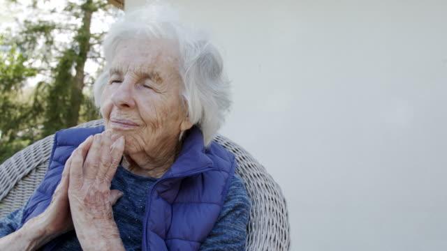 夏の屋外の芝生の椅子で目を閉じて祈る手を折りたたんだ高齢の白人キリスト教徒の女性 - 尖り屋根点の映像素材/bロール