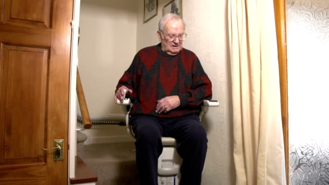 Elderly senior man using Stairlift Stair Lift in home