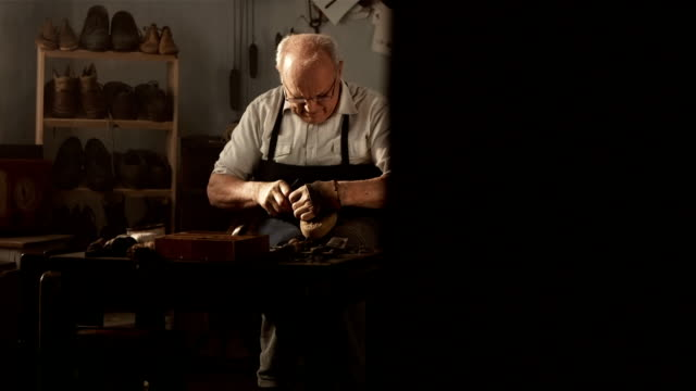 hd dolly: elderly shoemaker sewing the vamp - craftsperson stock videos & royalty-free footage
