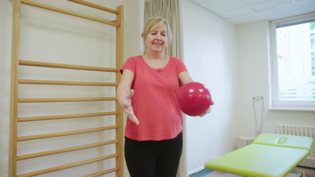 elderly smiling woman exercising with fitness ball - rehabilitation center stock videos & royalty-free footage