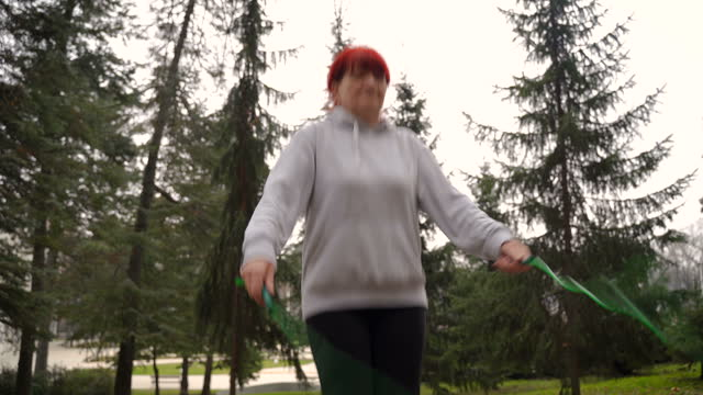 elderly sportswoman with jump rope in park - dieting stock videos & royalty-free footage