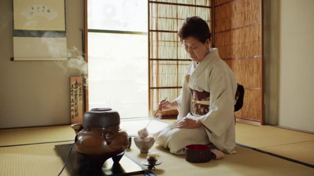 vídeos de stock, filmes e b-roll de anfitrião idoso da cerimónia de chá que mede para fora a água quente - washitsu