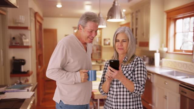 stockvideo's en b-roll-footage met elderly white couple reading a cellphone - natuurlijk haar