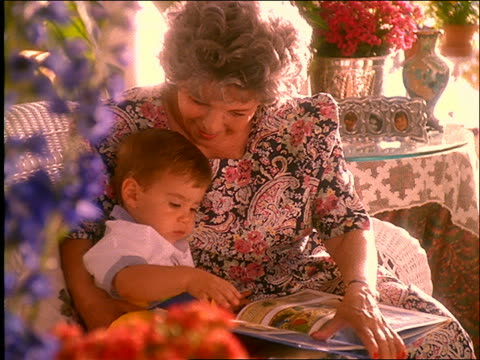 vidéos et rushes de elderly woman and small boy reading book - famille multi générations