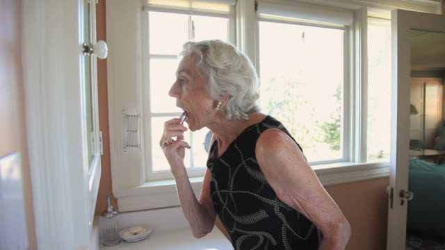 MS Elderly woman applying lipstick in front of mirror in bathroom / Portland, Oregon, USA