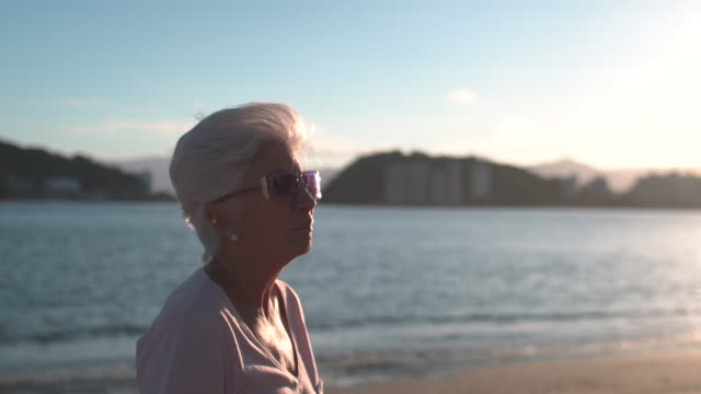 vídeos de stock, filmes e b-roll de elderly woman at the beach in a slow motion movement. - distante