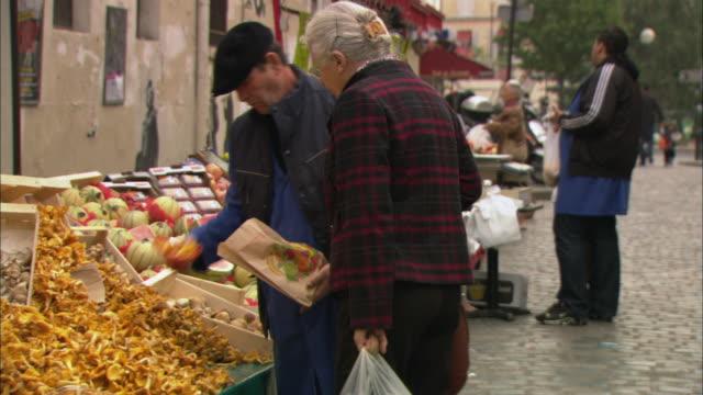 ms pan elderly woman buying chanterelles on street market / paris, france - francia video stock e b–roll