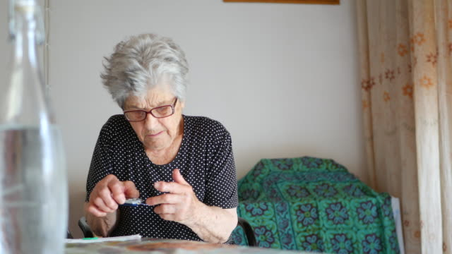 elderly woman checking her glucose levels - glucose stock videos & royalty-free footage
