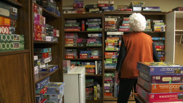 elderly woman choosing a jigsaw puzzle - jigsaw puzzle stock videos & royalty-free footage
