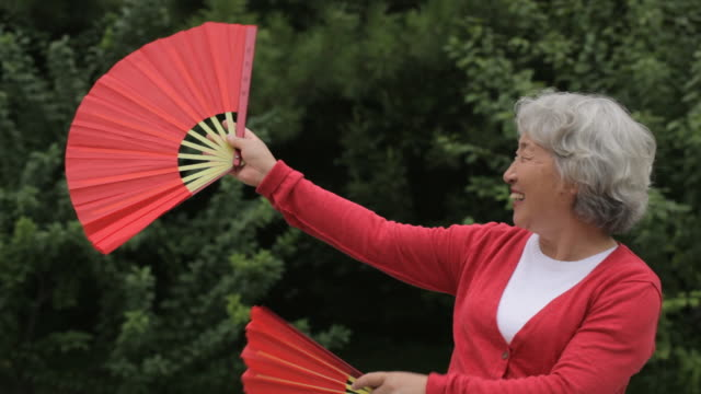 ms elderly woman dancing with red fans in park / china - hand fan stock videos and b-roll footage