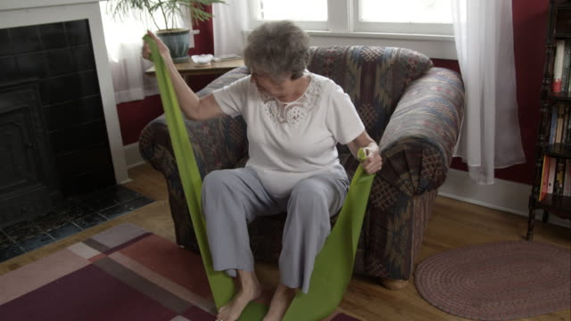 vidéos et rushes de elderly woman doing exercise with elastic bands at home. - chaise