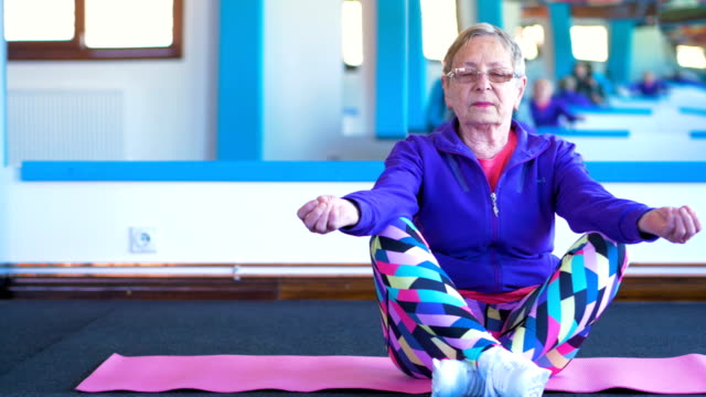 elderly woman doing yoga - woman cross legged stock videos & royalty-free footage