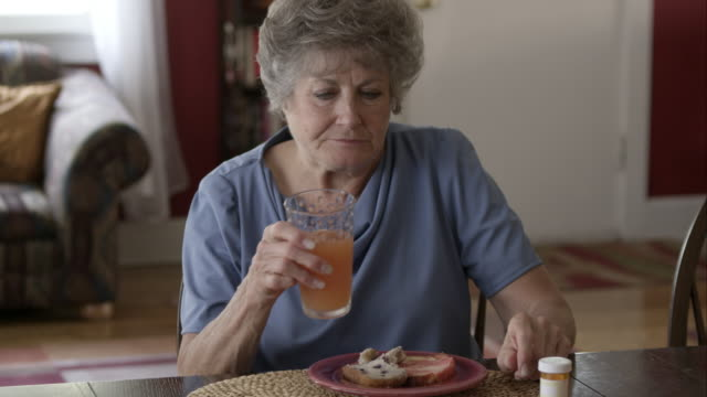 elderly woman eating breakfast and taking pills. - taking medicine stock videos and b-roll footage