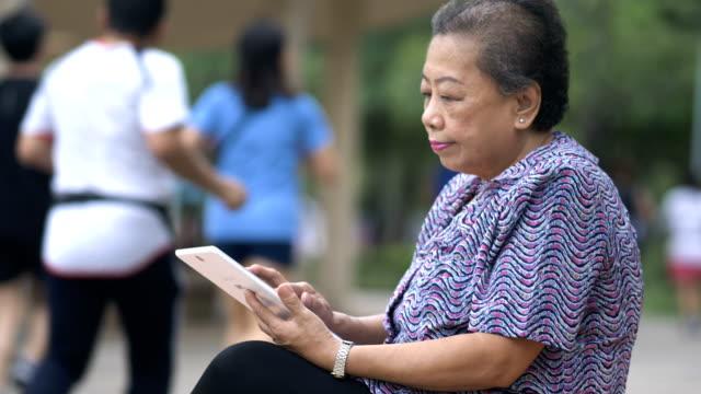 stockvideo's en b-roll-footage met oudere vrouw met een digitaal tablet buitenshuis - 65 69 jaar