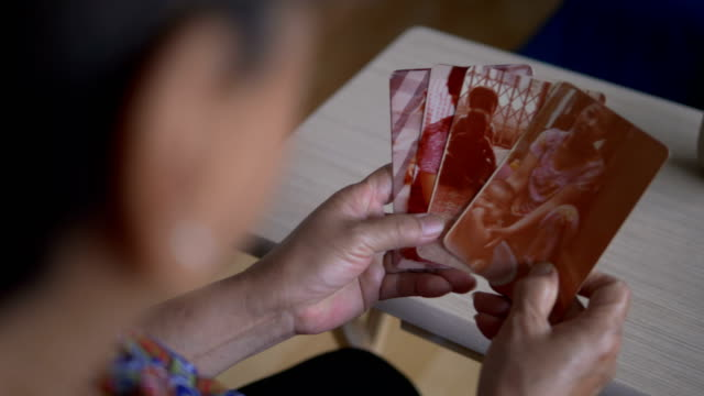 elderly woman holding old photo of baby - photo album stock videos and b-roll footage